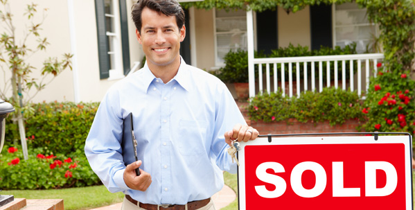 Real Estate Agent Next To a Sold Sign